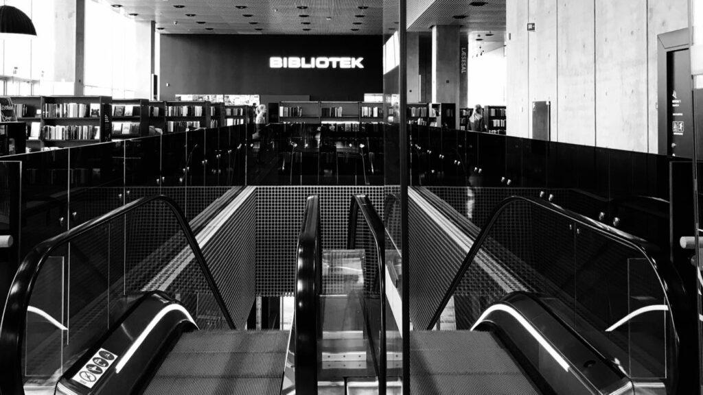 Kuvassa on liukuportaat tanskalaisessa kirjastossa. Kuvassa näkyy yleiskuvaa kirjastosta, kokoelmia ja kirjaston tilaa.
