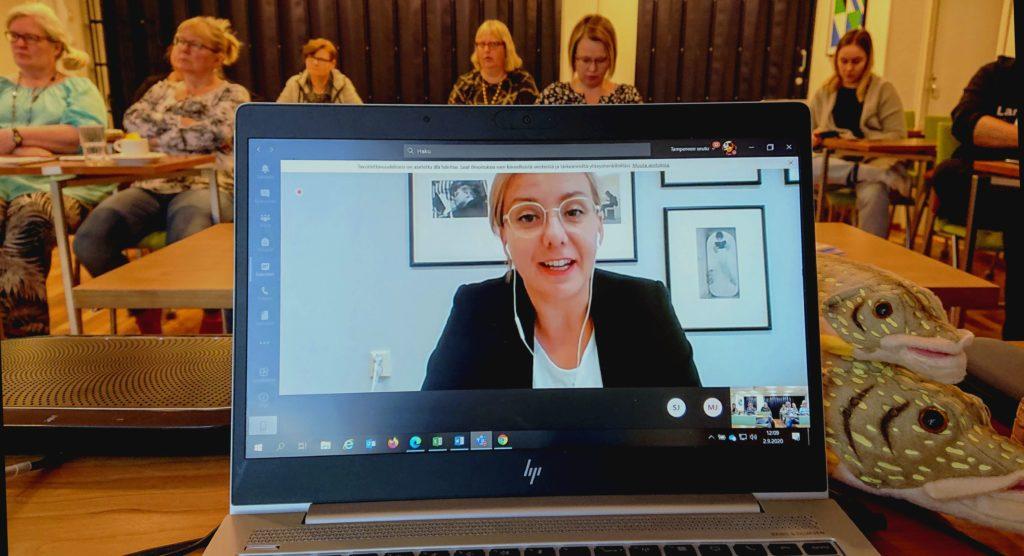 Kuvassa on Suomen kirjastoseuran toiminnanjohtaja Rauha Maarno tietokoneen näytöllä Teams-yhteydessä. Taustalla verkostopäivän osallistujia Muuramesta.