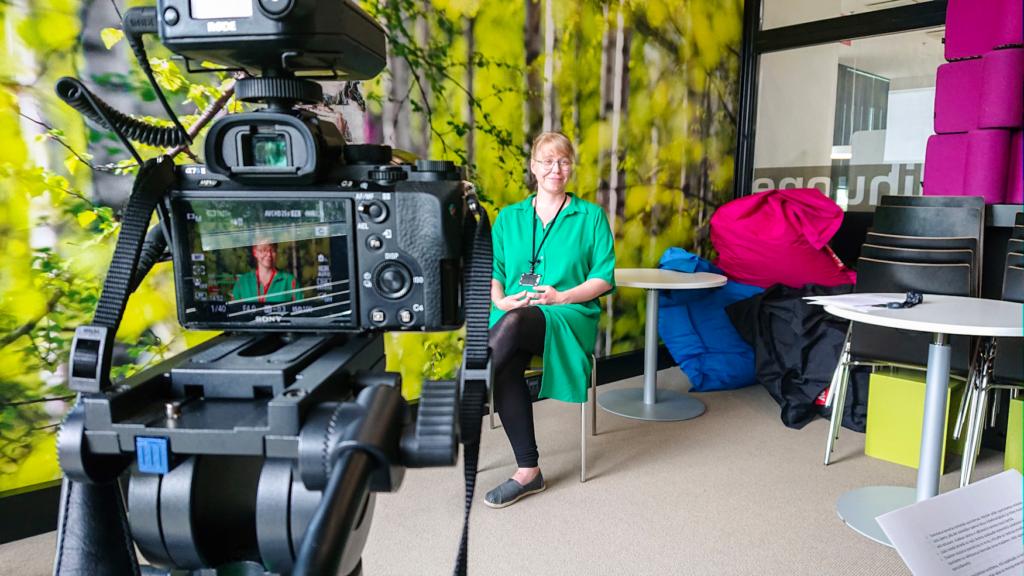 Making of -kuva videokuvauksista Lielahden kirjastossa. Kuvassa on kamera ja mediasihteeri Laura Aatola.