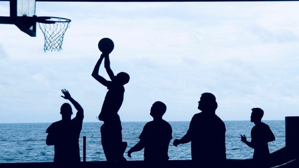 Kuvassa kuusi ihmistä pelaa yhdessä koripalloa meren rannalla.