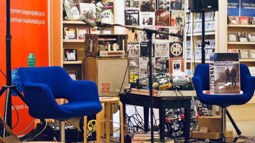 Kuvituskuva, jossa kuva Metso LIVE -kirjastotapahtuman lavasta. Lavalla tuoleja ja musiikkilaitteistoa.