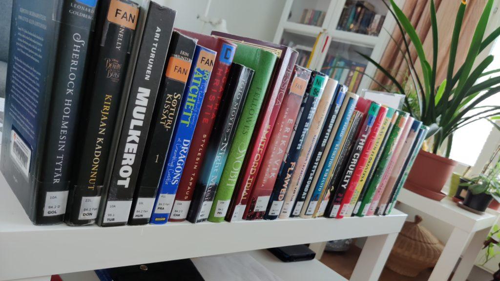 Kuvassa hyllyllinen kotiin kannettujen kirjojen selkämyksiä