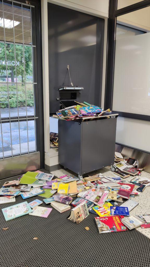 Kuvassa täysi palautuslaatikko, jonka ympärille lattialle on pudonnut kirjoja